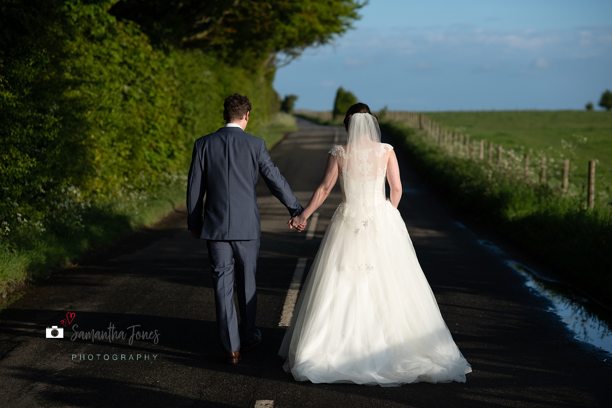 bride and groom walking along road in sunshine