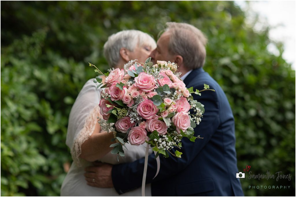 bride and groom kissing behind bouquet wedding Kent 2020
