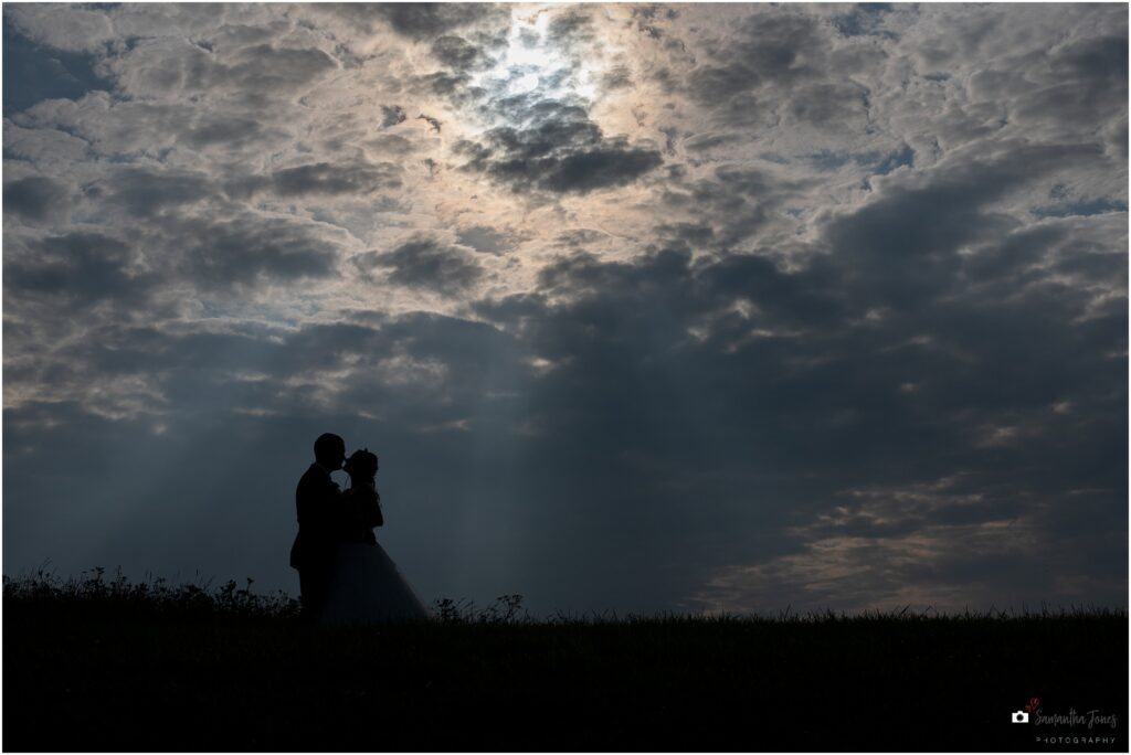 bride and groom portrait against dramatic sky after celebrant-led ceremony