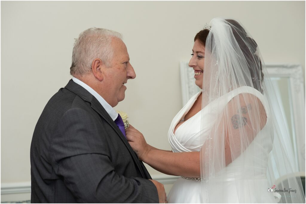 bride putting buttonhole on father