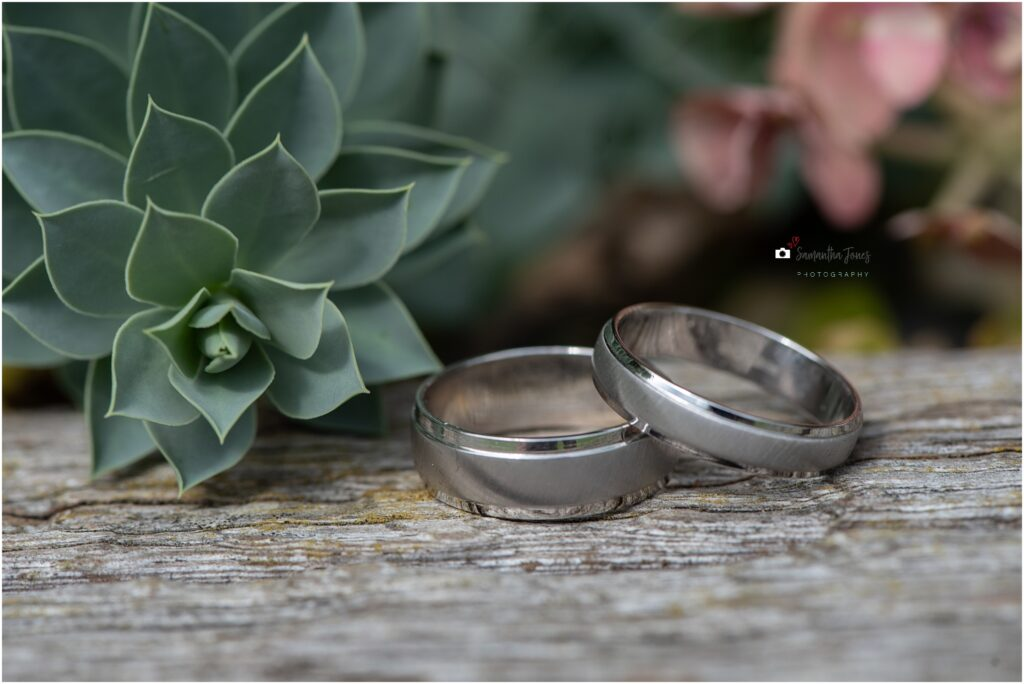 wedding rings with flowers and greenery behind